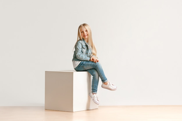 Portrait of cute little kid girl in stylish jeans clothes looking at camera and smiling, sitting against white studio wall. kids fashion concept