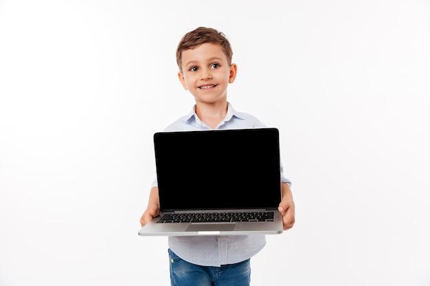 Portrait of a cute little kid showing blank screen laptop