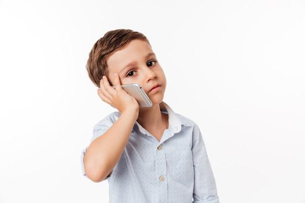 Portrait of a cute little kid talking on mobile phone