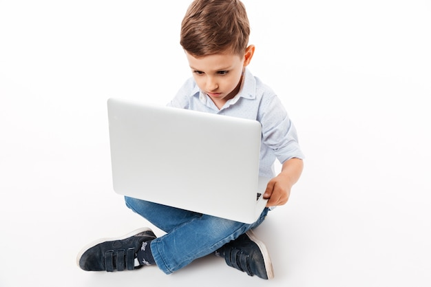 Portrait of a cute little kid using laptop computer