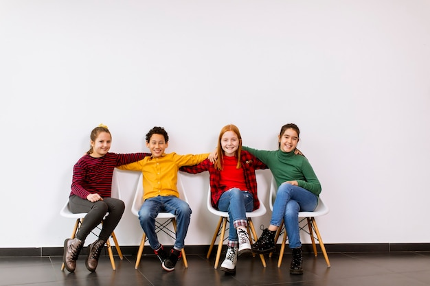 Portrait of cute little kids in jeans sitting in chairs against the white wall