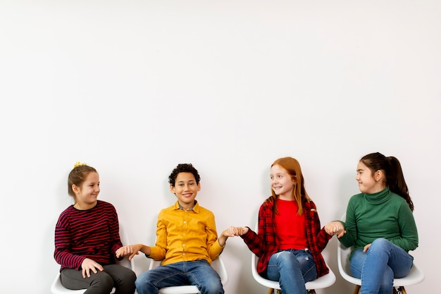 Portrait of cute little kids in jeans  sitting in chairs on white wall
