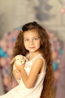 Portrait of cute little princess hold white rabbit in her hands. studio background with balls and cones.