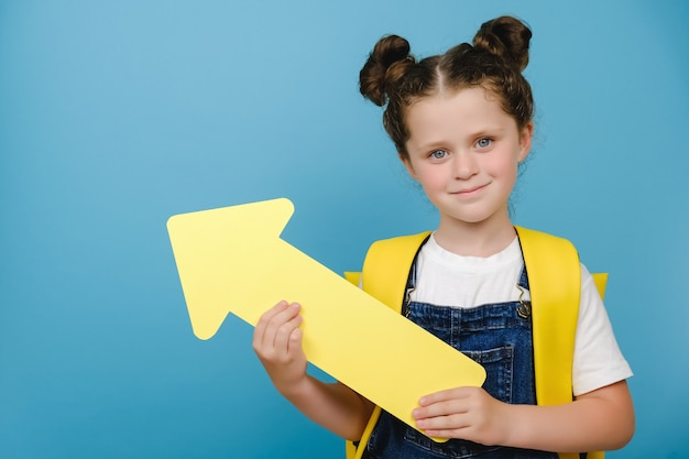 Portrait of cute little school girl holding yellow arrow pointing on copy space for promotional content, wears backpack, posing isolated over blue studio background wall. back to school concept