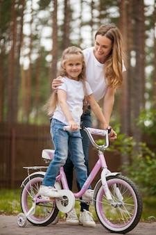 Portrait of cute little smiling girl daughter and mother riding bike bicycle in a courtyard on sunny summer day. active family leisure with kids.