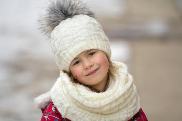 Portrait of cute little young funny pretty smiling blond child girl with gray eyes in nice warm winter clothing on white bright blurred outdoors copy space background. beauty of childhood concept.