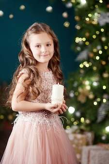 Portrait of cute long-haired little girl in dress on  of  lights. little girl holding burning candle. christmas, new year .