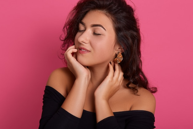 Portrait of cute lovely girl wearing black outfit with dark wavy hair, posing with closed eyes isolated on pink wall, attractive lady full of dreams.