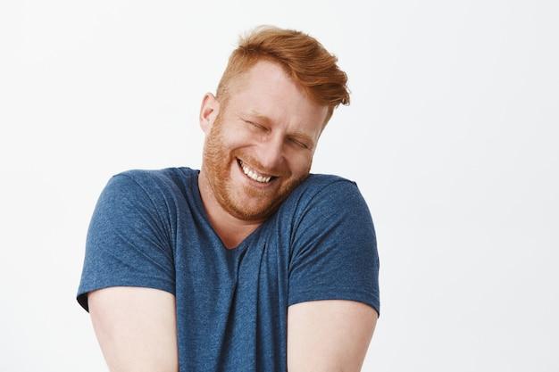 Ritratto di simpatico uomo rosso felice e soddisfatto felice e divertente in maglietta blu, alzando le spalle e appoggiando il viso sulla spalla mentre sorride ampiamente, arrossendo di gioia e felicità