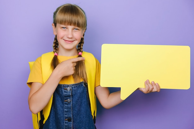 Portrait of cute positive caucasian school girl pointing on yellow speech bubble, wears backpack, posing isolated over purple color background in studio with copy space for promotion content. mockup