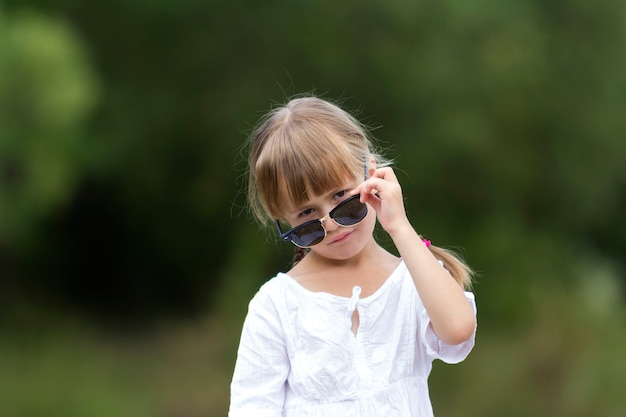 Portrait of cute pretty funny young girl with blond braids in white dress and dark sunglasses.