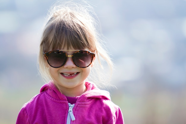Portrait of cute pretty little blond preschool girl in pink sweater and dark sunglasses smiling