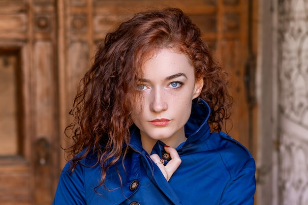 Portrait of cute red-haired girl , wavy hair and beautiful eyes