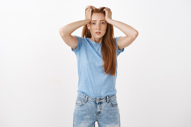 Portrait of cute redhead woman under pressure holding hands on head with perplexed and troubled look being tired and fed up of paper work sighing
