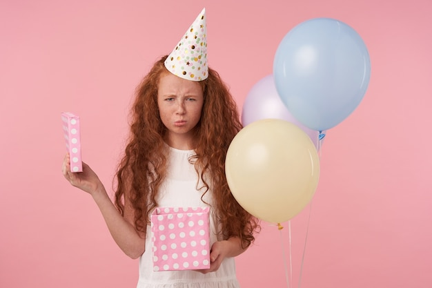 Portrait of cute sad female kid wearing festive clothes and birthday cap, looking in camera with unpleased face, going to cry because of bad gift, isolated over pink studio background