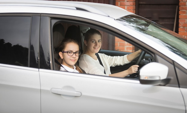 Portrait of cute schoolgirl going with mother to school by car