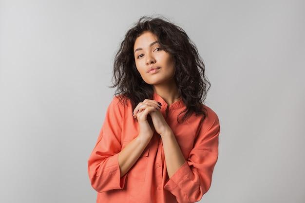 Ritratto di bella donna timida carina in camicia elegante arancione, capelli ricci, sorridente, tenendo le mani insieme, isolato