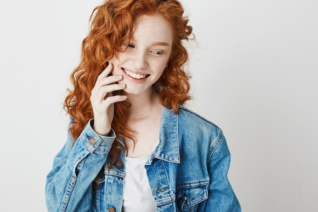 Portrait of cute shy redhead girl smiling looking in side . copy space.