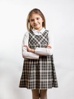 Portrait of cute shy schoolgirl in checkered dress against white background