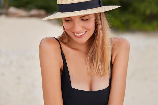 Ritratto di donna timida carina con espressione felice indossa costume da bagno nero e cappello estivo, ha una pelle sana abbronzata.