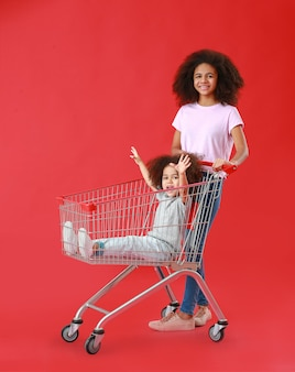Portrait of cute sisters with shopping cart on color surface