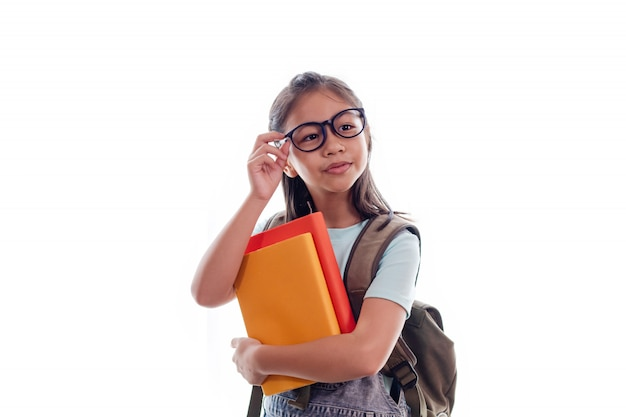 Portrait of cute smart asian schoolgirl with stack of books and school backpack isolated