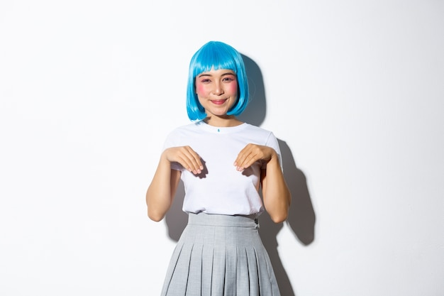 Portrait of cute smiling asian girl in blue wig and schoolgirl costume, playing around and acting like kitten, standing.