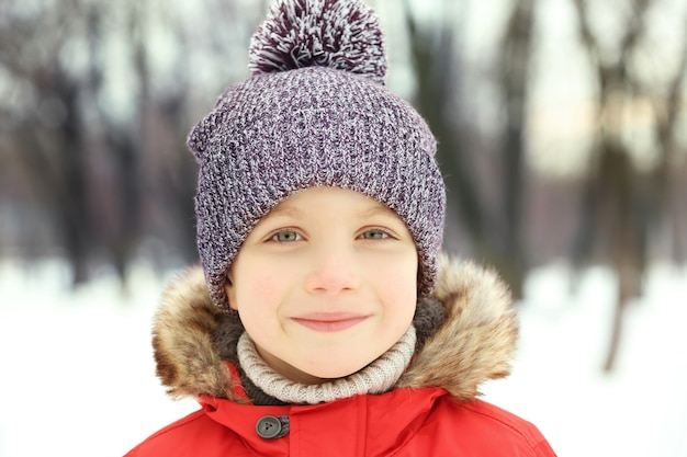 Portrait of cute smiling boy in beautiful warm outfit on winter background