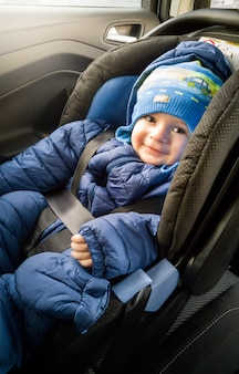 Portrait of cute smiling boy in hat sitting in car child seat