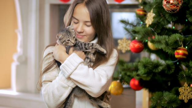 Portrait of cute smiling girl celebrating christmas with cute grey kitten