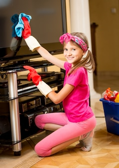Portrait of cute smiling girl cleaning tv screen with rag