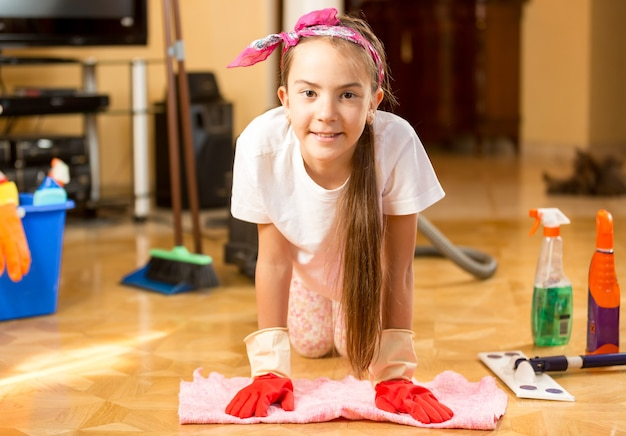 Portrait of cute smiling girl cleaning wooden floor with rag