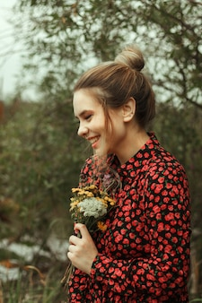 Portrait of a cute smiling girl in a dress with red flowers, which holds a bouquet of wildflowers in her hands.