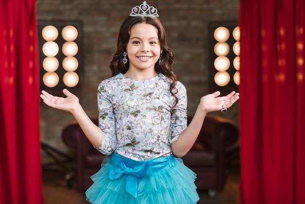 Portrait of cute smiling girl wearing crown standing in studio