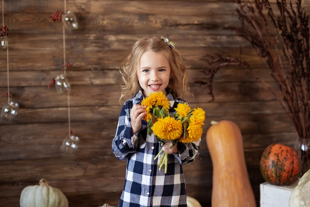 Portrait of cute smiling girl with bouquet of yellow flowers
