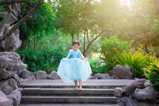 Portrait of cute smiling little girl in princess costume walking down the stairs in the park