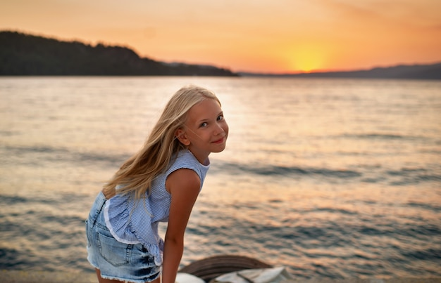 Portrait of a cute smiling little girl with glasses.a girl in shorts and a blue tshirt at sunset by the sea.turkey.