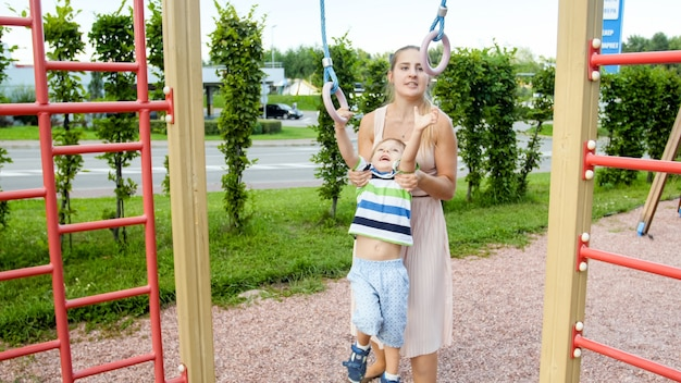 Portrait of cute smilling toddler boy hanging on the rings with his mother on children playground