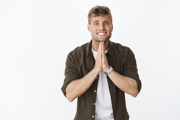 Portrait of cute and stylish young european boyfriend with blond hair and blue eyes smiling while begging, holding hands in pray hopeful as asking favour or help
