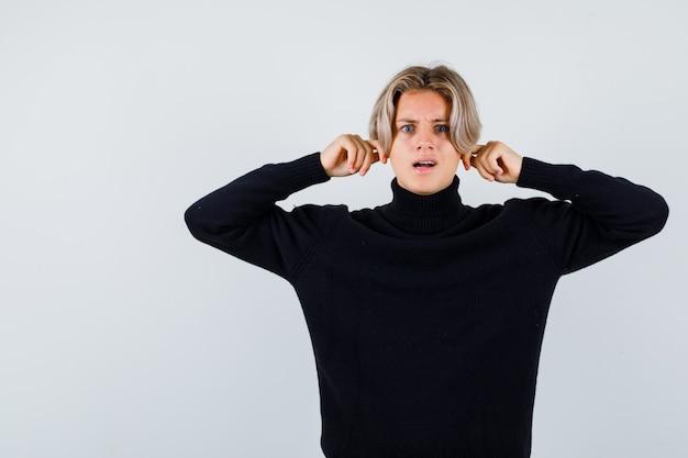 Ritratto di un ragazzo adolescente carino che si tira giù i lobi delle orecchie con un maglione a collo alto nero e sembra una vista frontale perplessa