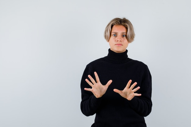 Ritratto di un ragazzo adolescente carino che mostra un gesto di resa con un maglione a collo alto nero e sembra spaventato vista frontale