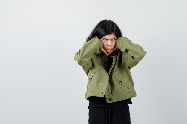 Ritratto di ragazza adolescente carina imbronciata con le guance appoggiate sulle mani, guardando lontano in giacca verde militare e guardando vista frontale pensierosa
