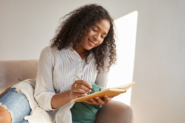 Portrait of cute teenage girl of african origin sitting comfortably on sofa with copybook, making drawings or sketches, having inspired joyful look. stylish young black woman writing in her diary