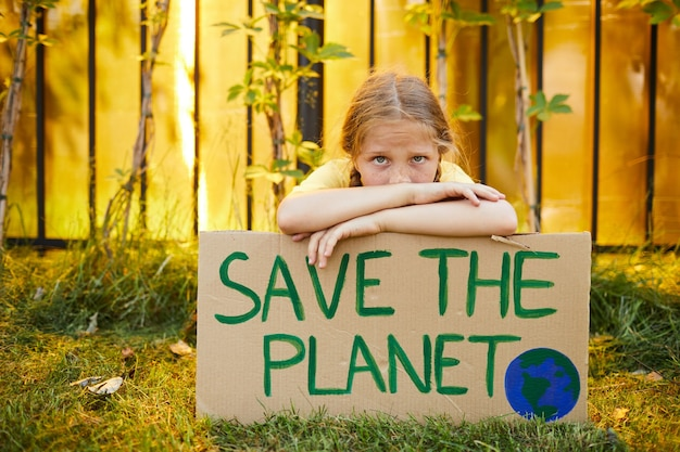 Portrait of cute teenage girl holding save the planet sign and looking at camera while protesting for nature outdoors, copy space