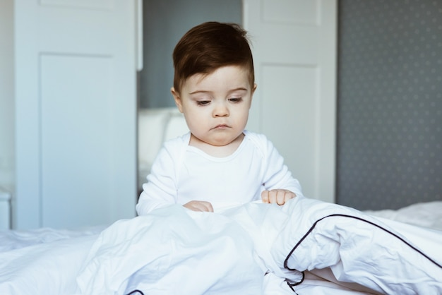 A portrait of a cute toddler baby boy in a white bodyuit seating on bed .baby in bedroom at home,ready to sleep side view