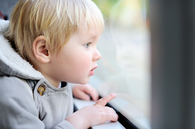 Portrait of cute toddler boy looking out train or tram window
