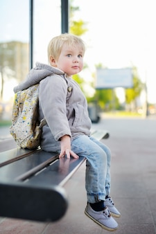 Portrait of cute toddler boy sitting on bench on bus stop