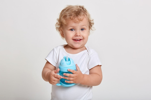 Portrait of cute toddler holding water bottle, kid playing with blue baby cup