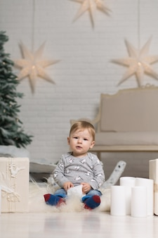 Portrait of a cute toddler playing on the floor near a christmas tree. merry christmas and happy holidays.
