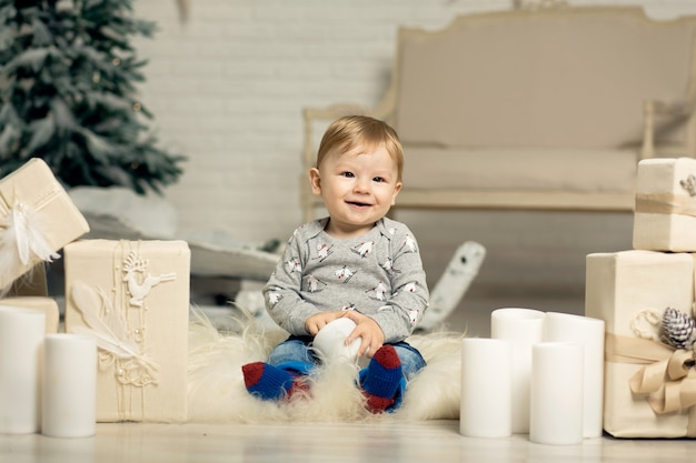 Portrait of a cute toddler playing on the floor near a christmas tree. merry christmas and happy holidays
